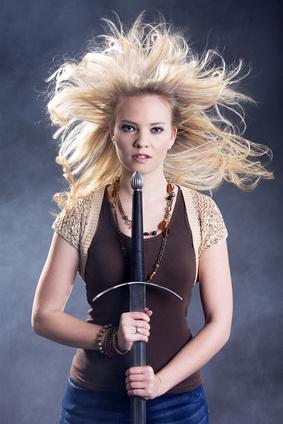 Junge Frau mit Schwert im Nebel und fliegende Haare